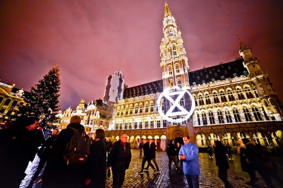Extinction Rebellion logo projected onto the Grand Place, Brussels