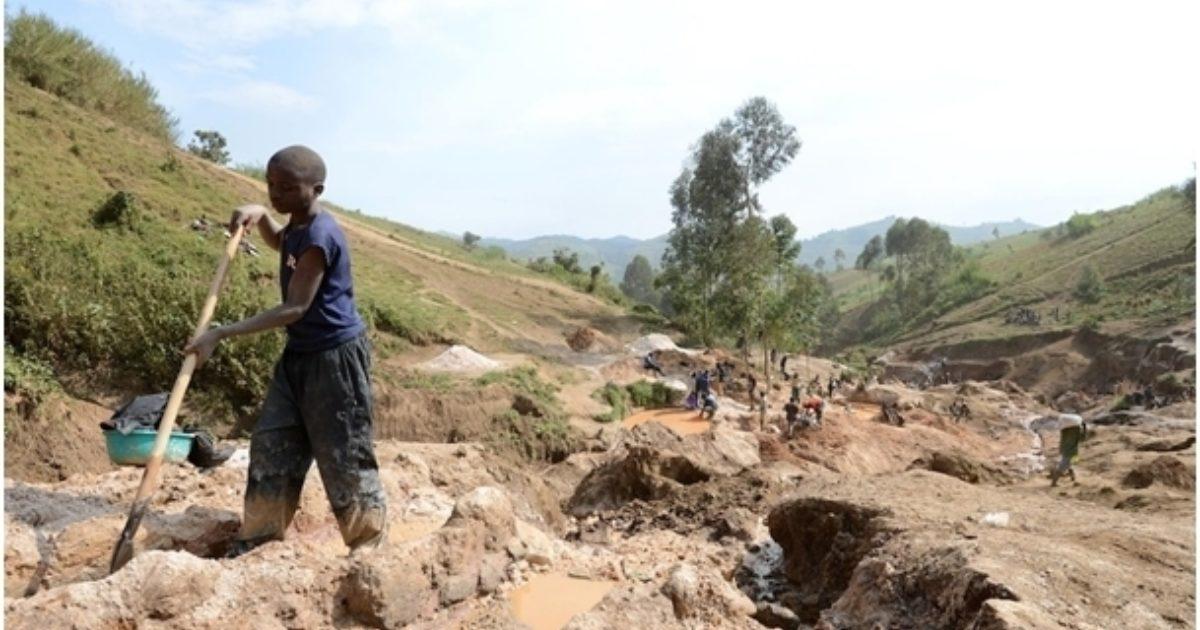 Un enfant sépare du minerai de la roche et du sable