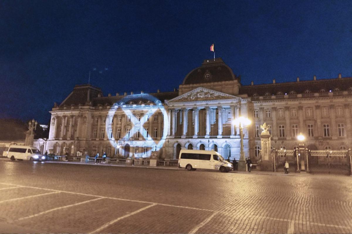 Logo Extinction Rebellion geprojecteerd op het Koninklijk Paleis, Brussel